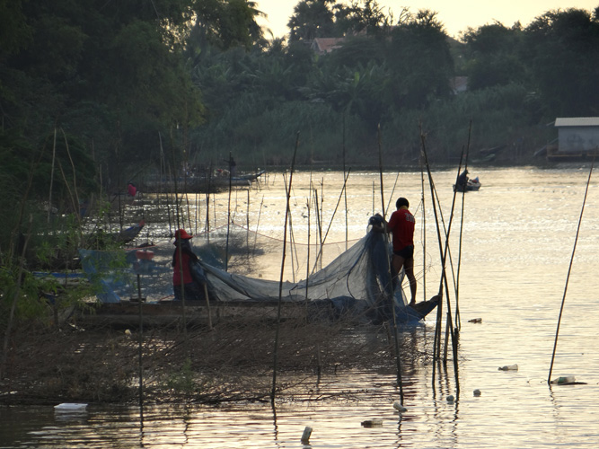 Fishermen setting nets along the bank of the river.